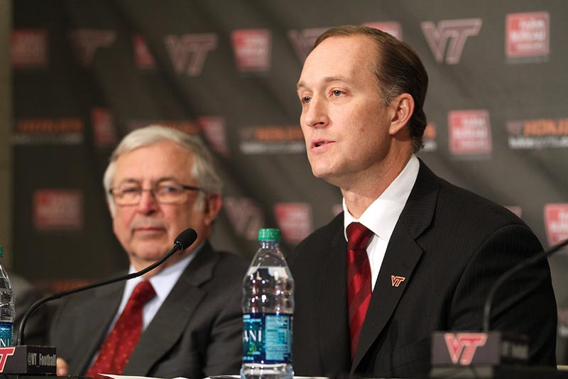 New Virginia Tech AD Whit Babcock talks to the media as Charles Steger looks on.