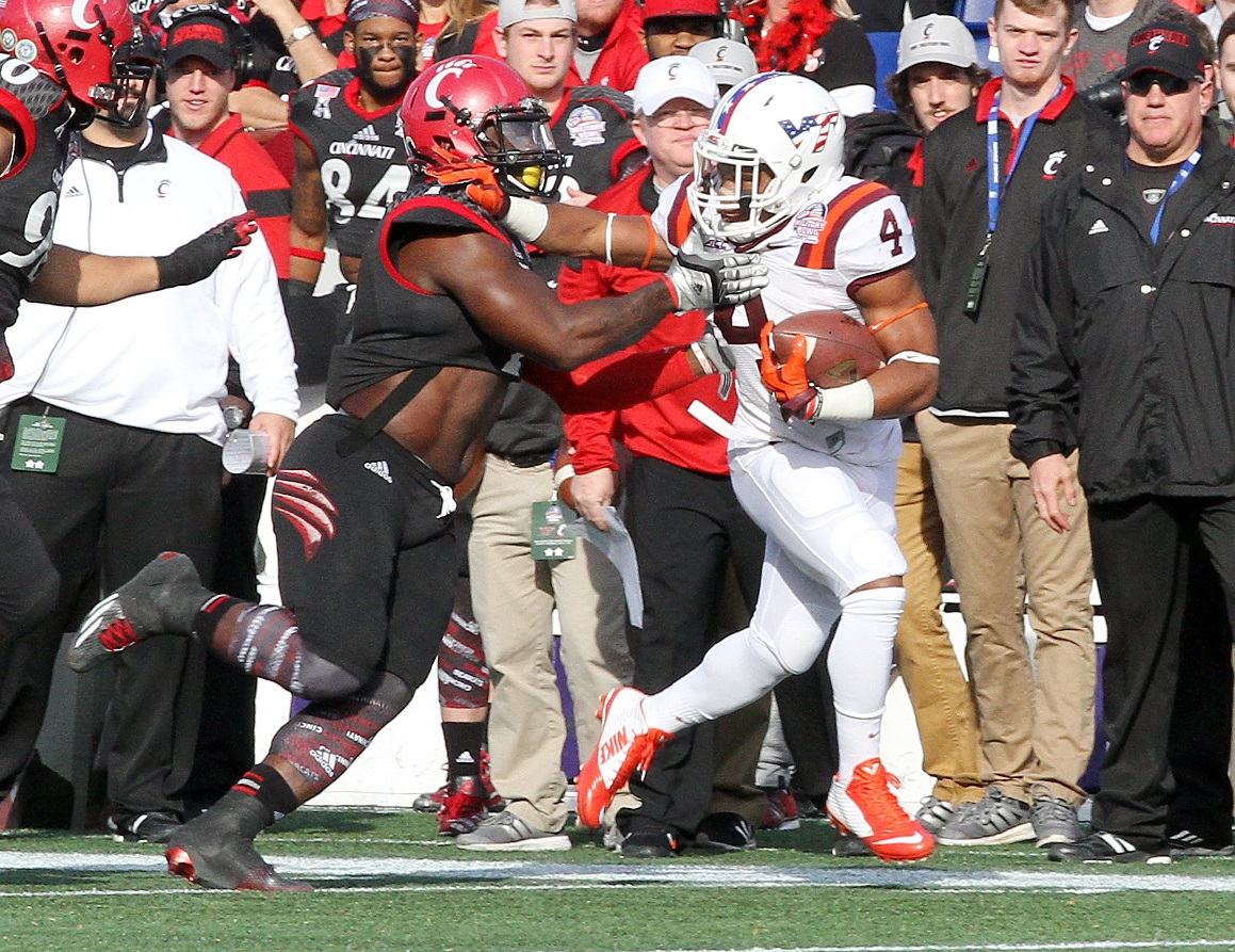J.C. Coleman, who rushed for a VT bowl record 157 yards, fends off a Cincinnati defender.