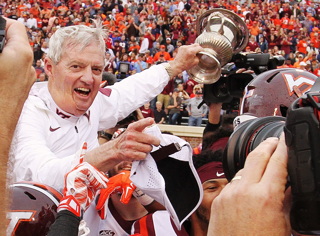 Frank Beamer celebrates with the Commonwealth Cup after the Hokies downed Virginia, 23-20.