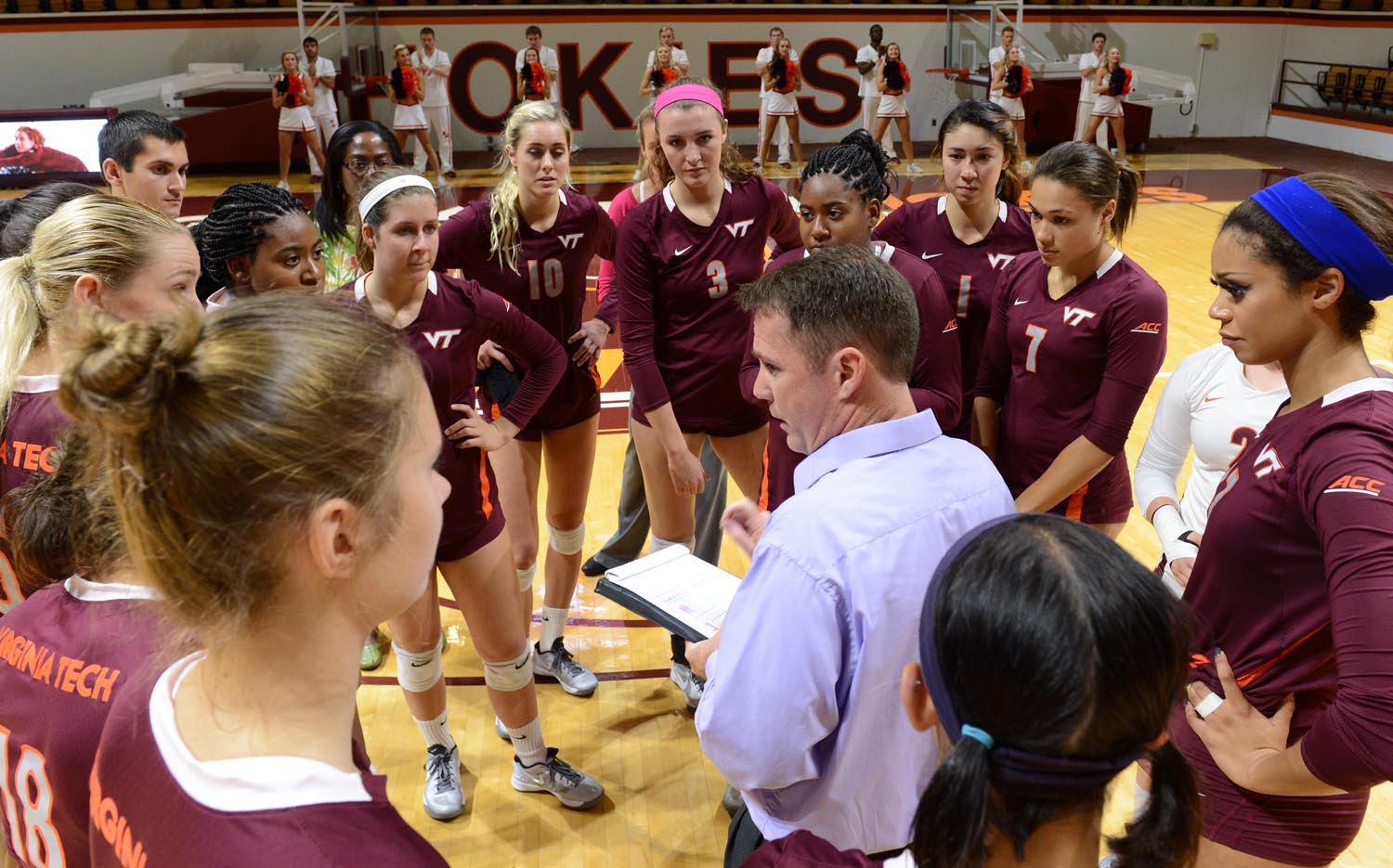 The Virginia Tech volleyball team surrounds head coach Chris Riley at a match in Cassell Coliseum